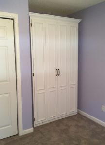 Twin painted Murphy bed in tiny space. with bifold doors