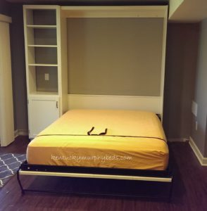 White painted panel bed with one accessory bookshelf-cabinet, open view