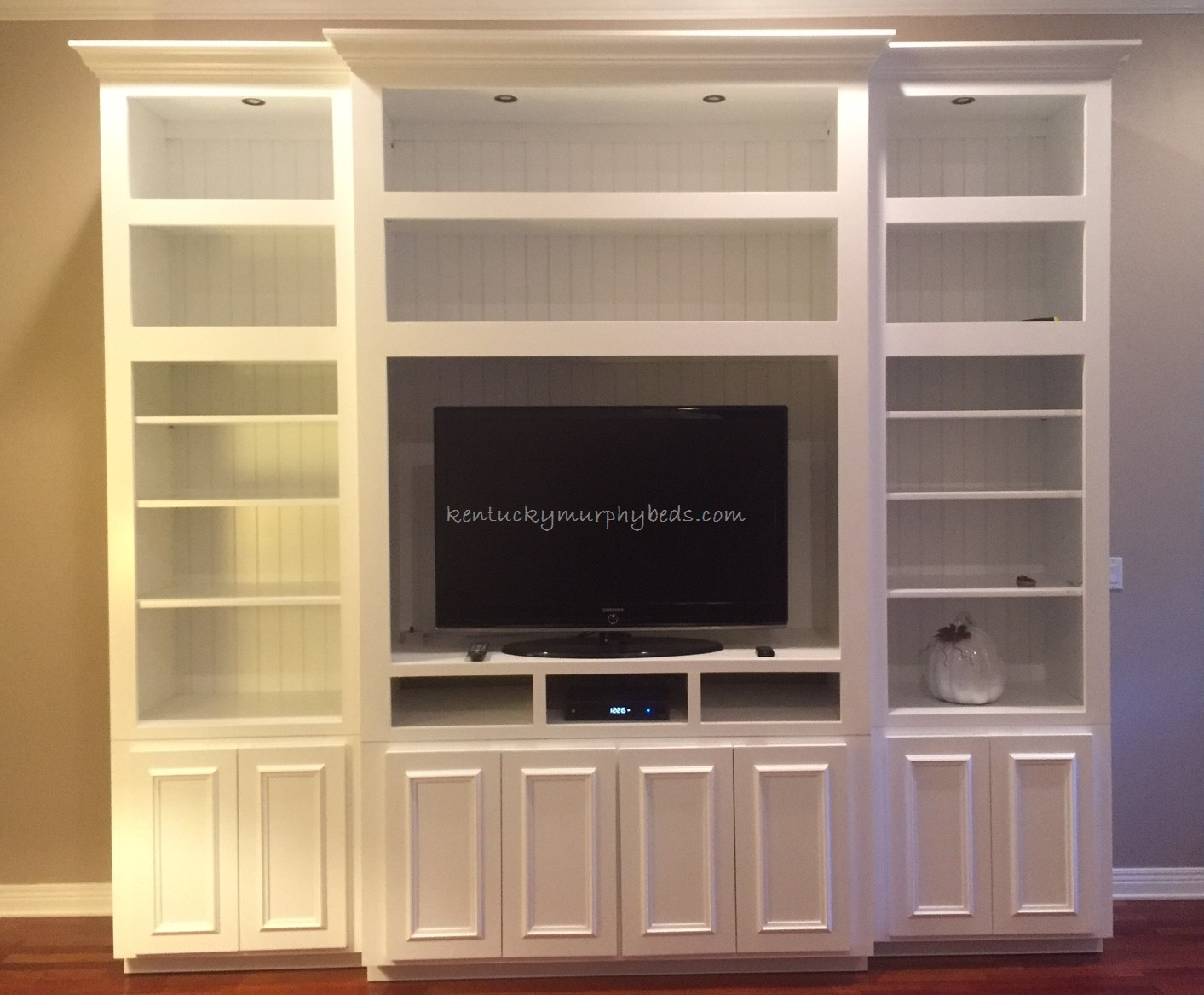 Entertainment Center of painted white MDF; open and closed cabinets; can lights