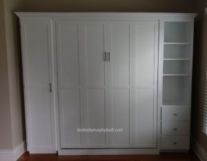 White painted queen panel door Murphy bed with shaker trim and crown molding, a side cupboard with one door and a side bookcase-drawer combo - closed view