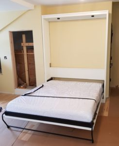 white painted panel door Murphy bed shown open in small second floor space