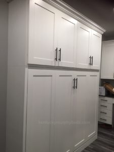 Horizontal full size Murphy bed cabinet with top cupboard maximizes the space in a long laundry/storage room